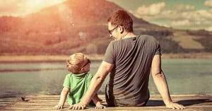 papa e hijo sentados en un muelle viendo el lago y sonriendo