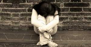 mujer sentada en acerca brocal tristeza